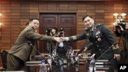 Jenderal Korea Selatan Kim Do-gyun (kanan) berjabat tangan dengan Letnan Jenderal An Ik San dari Korea Utara, di kota perbatasan Panmunjom, Korea Utara, 26 Oktober 2018. (Korea Pool / Yonhap melalui AP)