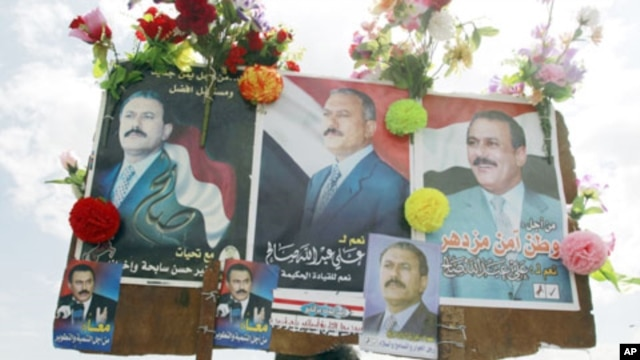 A supporter of Yemen's President Ali Abdullah Saleh holds up posters of Saleh after a rally to show support at the Tahrir Square in Sana'a, March 25, 2011