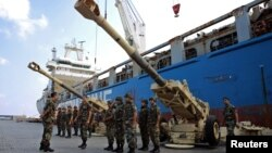 Lebanese troops stand near artillery pieces that were unloaded from a ship at Beirut port in Lebanon, Aug. 9, 2016.