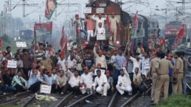 Demonstrators from the Samajwadi Party, a regional political party, shout slogans after they stopped a passenger train during a protest near Allahabad railway station, September 20, 2012.