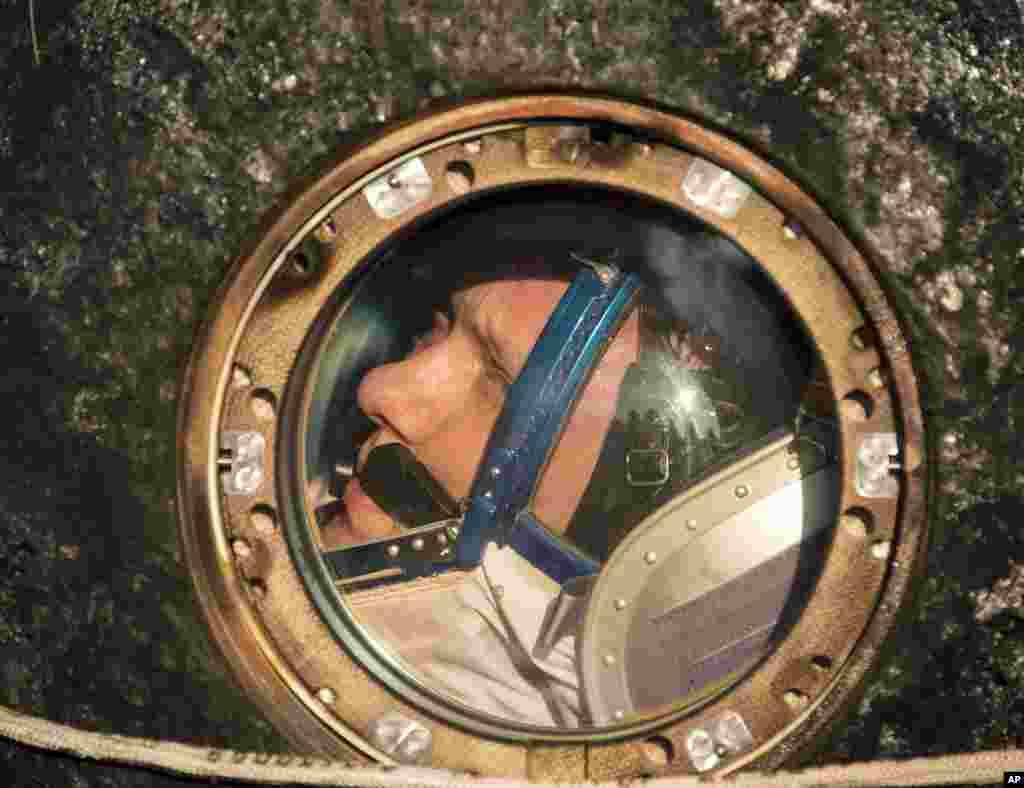 Expedition 40 Flight Engineer Oleg Artemyev of the Russian Federal Space Agency (Roscosmos) looks out the window of the Soyuz Capsule. Sept. 11, 2014