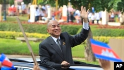 FILE-Cambodia's King Norodom Sihamoni waves from a vehicle to students during the Independence Day celebrations in Phnom Penh, Cambodia, Monday, Nov. 9, 2015.
