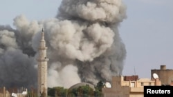 Smoke rises over the Syrian town of Ras al-Ain after an air strike November 13, 2012.