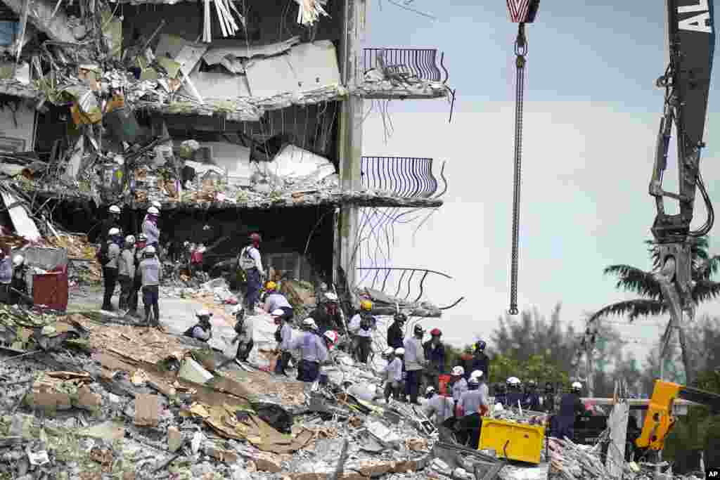 Rescue workers search in the rubble at the Champlain Towers South condominium in the Surfside area of Miami, Florida.