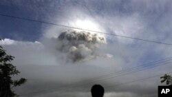 ຊາຍຊາວອິນໂດເນເຊຍຜູ້ນຶ່ງ ກໍາລັງຢືນເບິ່ງການລະເບີດຂອງພູໄຟ Mount Merapi ຢູ່ Kepuharjo ໃກ້ເມືອງ Yogykarta ໃນພາກກາງຂອງເກາະຈາວາ ໄດ້ຜົນອາຍຂີ້ເຖົ່າປິວກະຈາຍຂຶ້ນໄປເທິງອາກາດໃນວັນພຸດ ທີ 03 ພະຈິກ 2010 ເປັນຕົ້ນມາ. (AP Photo/Gembong Nusantara)