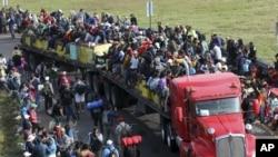 Los migrantes centroamericanos se suben a un remolque de dieciocho ruedas, en Irapuato, México, el lunes 12 de noviembre de 2018.