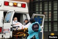 Técnicos de emergencias médicas suben a un paciente en una ambulancia fuera del Centro Hospitalario Elmhurst,en Nueva York, en medio de un brote de la COVID-19.