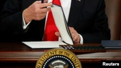 U.S. President Donald Trump prepares to sign an executive order at Homeland Security headquarters in Washington, Jan. 25, 2017.