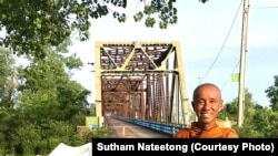 Buddhist monk Sutham Nateetong is taking a picture on rout 66 during his walking trip across the US to promote peace.