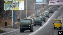 Unmarked military vehicles travel along a road outside the separatist rebel-held town Makiivka, 25 km (16 miles) from Donetsk, eastern Ukraine, Nov. 8, 2014