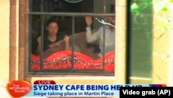 This image taken from video shows people holding up hands inside a cafe in Sydney, Australia, Dec. 15, 2014.