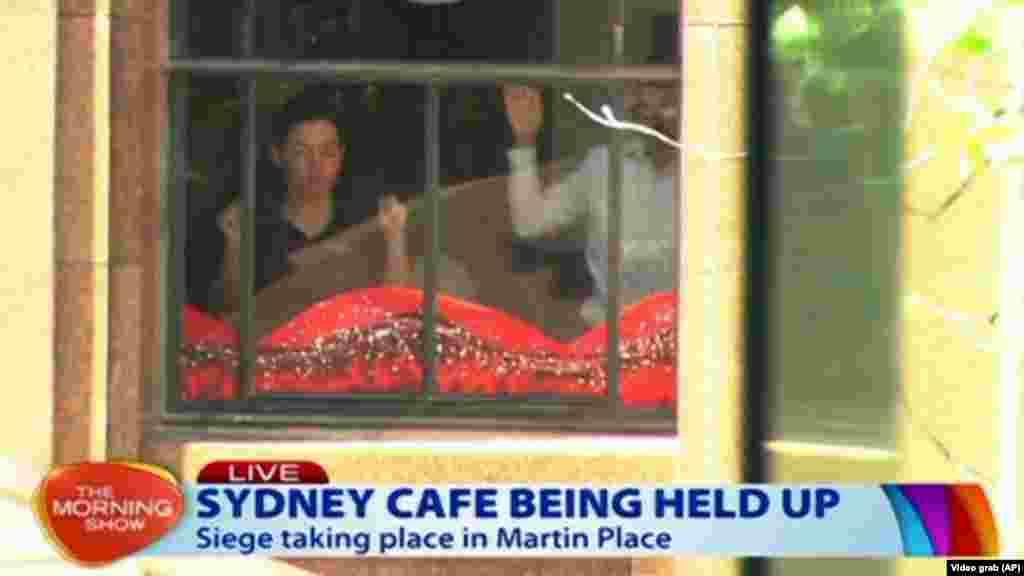 Dos de los rehenes con las manos en alto dentro de la cafetería.