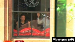 FILE - This image taken from video shows people holding up hands inside the Lindt Chocolate Cafe in Sydney, Dec. 15, 2014.