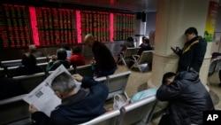 Các nhà đầu tư theo dõi giá cổ phiếu tại một trung tâm môi giới chứng khoán ở Bắc Kinh, ngày 5/1/2016.