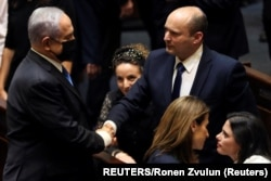 Benjamin Netanyahu (L) greets new Israel Prime minister Naftali Bennett following the vote on the new coalition at the Knesset, Israel's parliament, in Jerusalem June 13, 2021. (REUTERS/Ronen Zvulun)