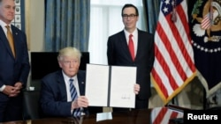 U.S. President Donald Trump displays a financial services executive order as Treasury Secretary Steven Mnuchin looks on during a signing ceremony at the Treasury Department in Washington, April 21, 2017.