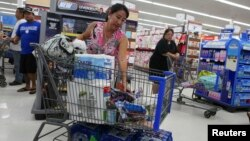 Shelly Nakasone looks through her shopping cart as she buys supplies as a hurricane and a tropical storm approach the Hawaiian islands, in Mililani, Hawaii, Aug. 5, 2014.