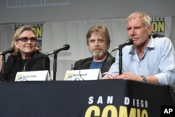 "FILE - Carrie Fisher, Mark Hamill, and Harrison Ford attend Lucasfilm's ""Star Wars: The Force Awakens"" panel on day 2 of Comic-Con International in San Diego, Calif., July 10, 2015."
