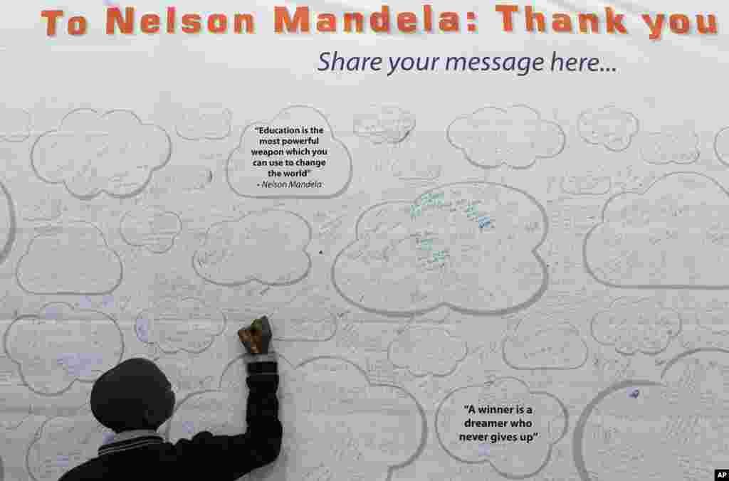 Em Thabiso Boya viết lời chúc mau hồi phục lên một bích chương lớn cho Cựu Tổng thống Nam Phi Nelson Mandela, tại một cuộc triển lãm giáo dục ở Johannesburg, Nam Phi. Ông Mandela, vẩn còn nằm trong bệnh viện tới ngày thứ 13 vì bệnh sưng phổi tái phát.