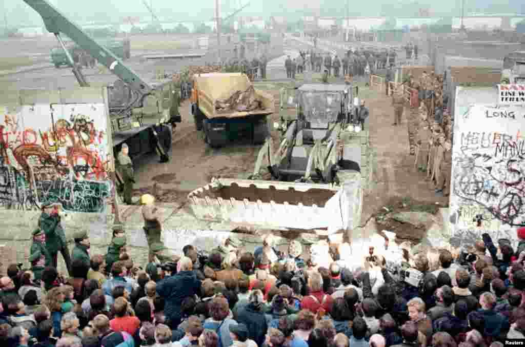 12 نومبر 1989 کو لی گئی ایک تصویر جس میں مشرقی جرمنی کے زیر استعمال رہنے والا ایک بلڈوزر اور کرین برلن وال کو مسمار کرتے ہوئے دیکھا جاسکتا ہے۔