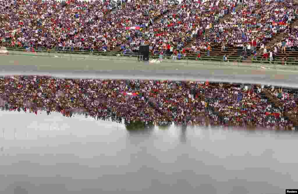 Fans of Cambodia's soccer team are reflected in a puddle of water at a 2018 World Cup qualifying soccer match between Cambodia and Afghanistan at the Olympic Stadium in Phnom Penh.