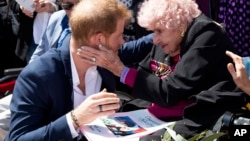 Britain's Prince Harry is embraced by 98-year-old Daphne Dunne during a walkabout outside the Opera House in Sydney, Australia, Oct. 16, 2018.