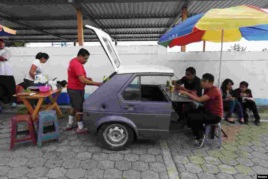 People have breakfast near a polling station in Mixco, Guatemala, Oct. 25, 2015. Playing up his outsider status and promising a clean government, 46-year-old Jimmy Morales, a former TV comedian, swept to power in the presidential election after milking public anger over a corruption scandal that deepened distrust of the political establishment.