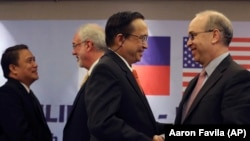 U.S. Assistant Secretary of State Daniel Russel, right, shakes hands with Philippine Undersecretary of Foreign Affairs Evan P. Garcia,after their press conference on the fifth Philippines-United States Bilateral Strategic Dialogue in Manila, Philippines Wednesday, Jan. 21, 2015. (AP Photo/Aaron Favila)