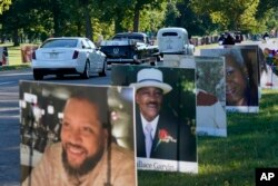 A procession of vehicles drive past photos of Detroit victims of COVID-19, Monday, Aug. 31, 2020 on Belle Isle in Detroit.