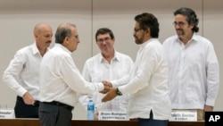 Humberto de la Calle, izquierda al frente, jefe del equipo de negociadores del gobierno colombiano da la mano a Iván Marquez, jefe negociador de las Fuerzas Armadas Revolucionarias de Colombia, FARC, tras la firma en Cuba de un pre-acuerdo -en diciembre 15 de 2015- sobre las reparaciones a 6 millones de víctimas del conflicto colombiano.