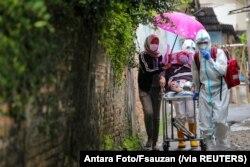 Para tenaga kesehatan dengan mengenakan alat pelindung diri membawa pasien Covid-19 di tengah pandemi virus corona di Jakarta, 13 Desember 2020. (Foto: Antara Foto/Fsauzan via Reuters)