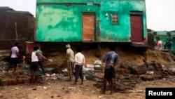 Para nelayan membersihkan puing-puing dari rumah mereka yang rusak akibat dihantam Siklon Phailin di wilayah Puri, bagian timur negara bagian Odisha (14/10).