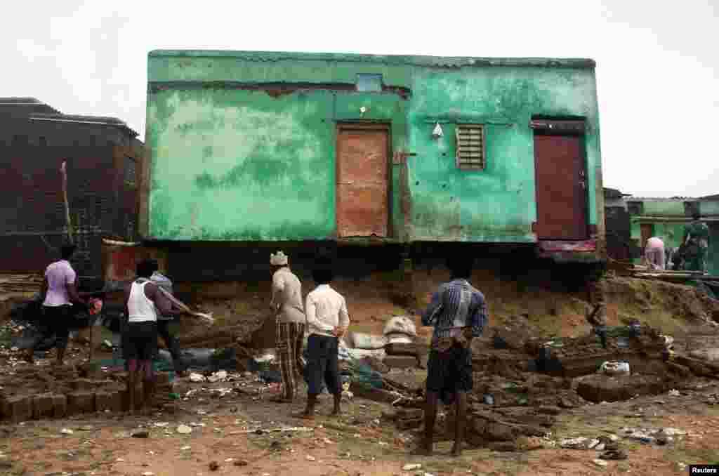 Fishermen clear debris from their damaged houses after Cyclone Phailin hit Puri in the eastern Indian state of Odisha, Oct. 14, 2013.