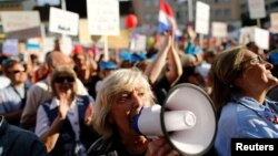 "A woman uses a megaphone during a protest billed ""Croatia can do better,"" against what demonstrators say is political meddling in education reform, on Zagreb's main square, Croatia, June 1, 2016."