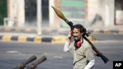 图为一名利比亚反政府武装人员8月17日携带火箭弹活动在迪黎波里以西大约50英哩处的塞卜拉泰