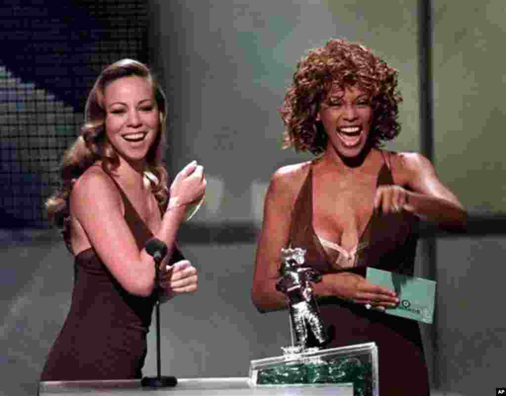 FILE - In this Sept. 10, 1998 file photo, Mariah Carey, left, and Whitney Houston present the award for Best Male Video during the MTV Video Music Awards, in Universal City, Calif. Whitney Houston, who reigned as pop music's queen until her majestic voice