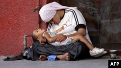 A Syrian refugee woman holds her child as they rest on the sidewalk of a street in the southern Lebanese city of Sidon.