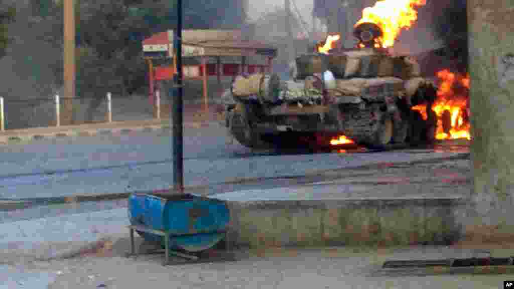 This citizen journalism image provided by The Syrian Revolution against Bashar Assad shows a Syrian military tank on fire during clashes in Joubar outside Damascus, Sept. 4, 2013.