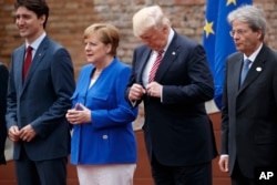 President Donald Trump adjusts his jacket during a family photo with G7 leaders at the Ancient Greek Theater of Taormina, Friday, May 26, 2017, in Taormina, Italy.