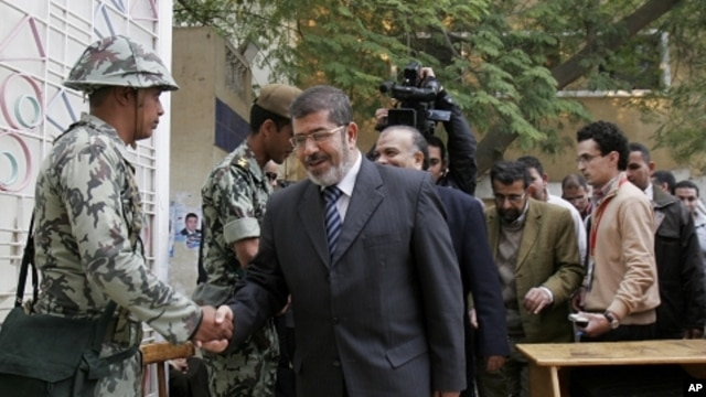 Muslim Brotherhood spokesman Mohammed Morsi shakes hands with a solider on the first day of parliamentary elections in Cairo, Egypt, Monday, Nov. 28, 2011.