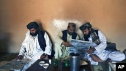 Pashtun men read local newspapers reporting the arrest of senior al Qaida leader Younis al- Mauritani at roadside tea shop in Quetta, Pakistan, September 6, 2011.