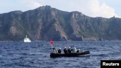 Sebuah perahu Penjaga Pantai Jepang (depan) dan kapal layar berisi sekitar 20 aktivis nasionalis dan nelayan Jepang berlayar ke kepulauan sengketa Senkaku di Timur Laut Cina (18/8).