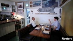 Canada's Prime Minister Justin Trudeau speaks with former United States President Barack Obama at a restaurant during Obama's visit to address the Montreal Chamber of Commerce, in Montreal, Quebec, June 5, 2017.