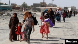 Residents who fled their homes due to fighting between Iraqi forces and Islamic State militants return to their village cleared by the Iraqi forces in western Mosul in Iraq, June 7, 2017.