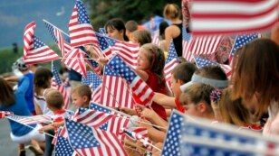 People wave flags as the Independence Day parade rolls down Main Street, July 4, 2014, in Eagar, Ariz.
