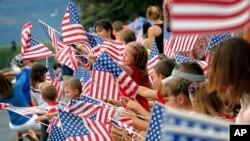 Người dân vẫy cờ trong buổi diễu hành Ngày Độc lập ở Eagar, bang Arizona năm 2014.