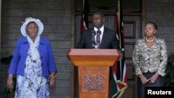 Kenya's Deputy President William Ruto (C) flanked by his wife Rachel Ruto (R) and mother Sarah Cherono (L) addresses a news conference on the ruling by the International Criminal Court (ICC) on the case against him and broadcaster Joshua Sang in Nairobi,