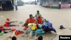 Regu penolong mendorong perahu karet dan mengevakuasi warga dari rumah mereka yang terkena banjir di wilayah Marikina, Manila, Filipina (7/8).