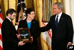 FILE - Then-President Bush, right, presents the Medal of Honor to parents of Army Pfc. Ross McGinnis, of Knox, Pennsylvania, in the East Room of the White House in Washington, June 2, 2008.