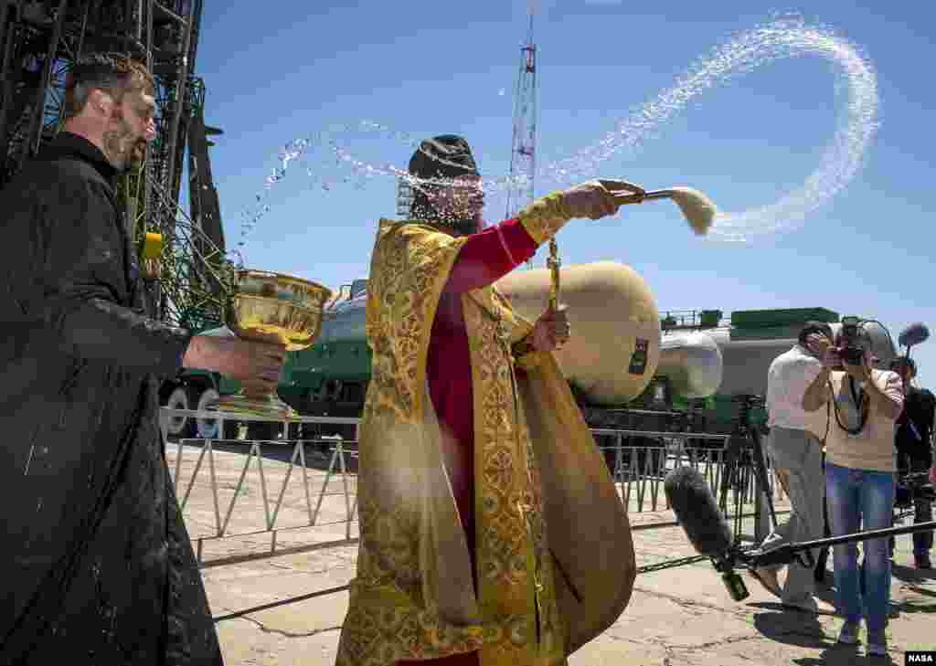 An Orthodox Priest blesses members of the media shortly after having blessed the Soyuz rocket at the Baikonur Cosmodrome Launch pad in Kazakhstan.